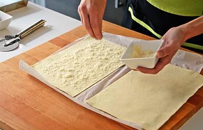 Cospargere la pasta sfoglia con il parmigiano